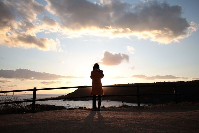 Rear view of silhouette woman standing against sky during sunset