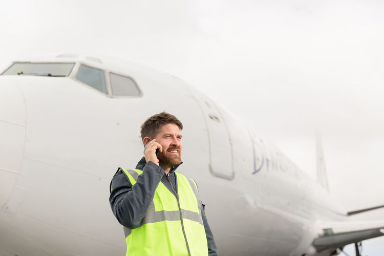 Man using mobile phone while sitting in airplane