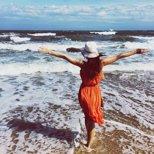 Rear View Of Woman With Arms Outstretched Standing At Sea Shore