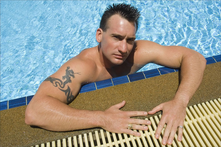 Young muscle man relaxing at swimming pool Arm Color Image Confidence  Hands Human Body Part Human Limb Hunk Looking At Camera Man Muscleman Person Photography Portrait Real People Shirtless Sport Swimming Swimming Pool Tattoo Well Being Young