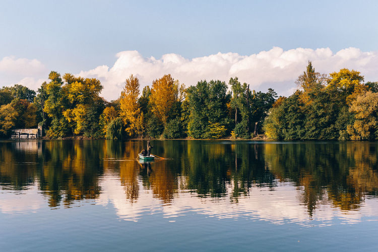 People Rowing Boat In Lake During Autumn