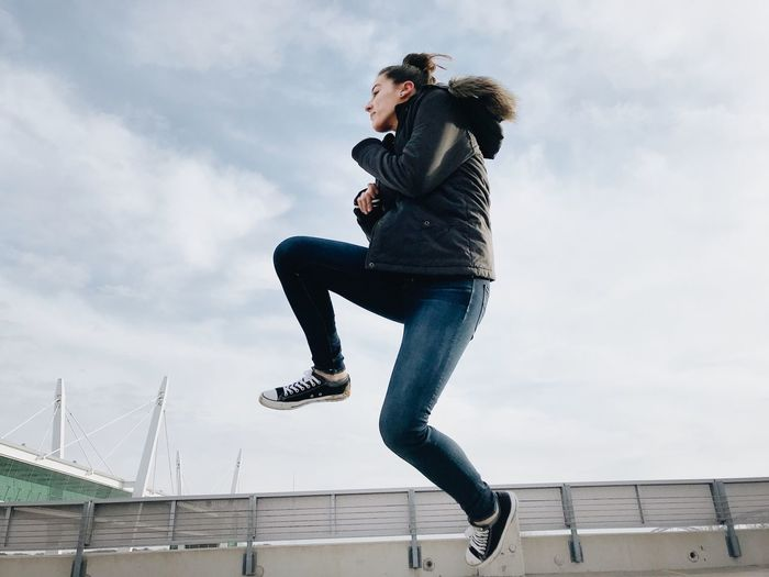 City Copy Space Exercise Woman Active Activity Casual Clothing Cloud - Sky Day Energetic Energy Female Jumping Lifestyles Mid-air Motion negative space One Person Outdoors Powerful Real People Sky Urban Young Adult Young Women
