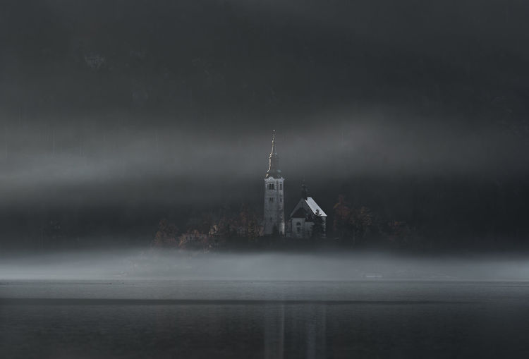 Old church on an island on the Bled lake, surrounded by morning fog and shadow, on a cold day of December, in Bled, Slovenia. Bled Slovenia Architecture Bled Church Building Building Exterior Built Structure Fog Fog Over Water Foggy Lake Lake Bled Landmark Landscape Nature Place Of Worship Tower Travel Destinations Water