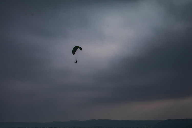 Low angle view of silhouette paragliding against sky