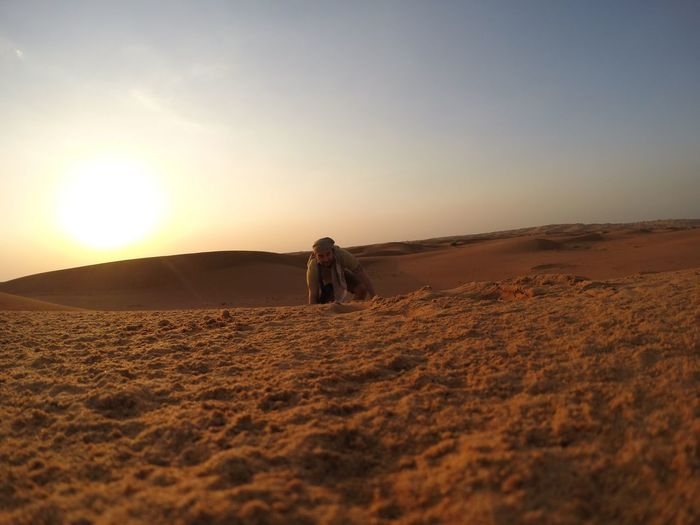 Man kneeling on sand dune against sky during sunset