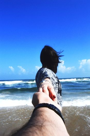 Woman holding cropped hand of man at beach