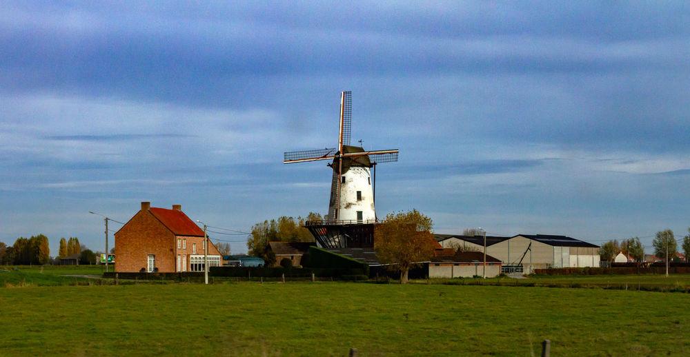 Windmill on field by buildings against sky