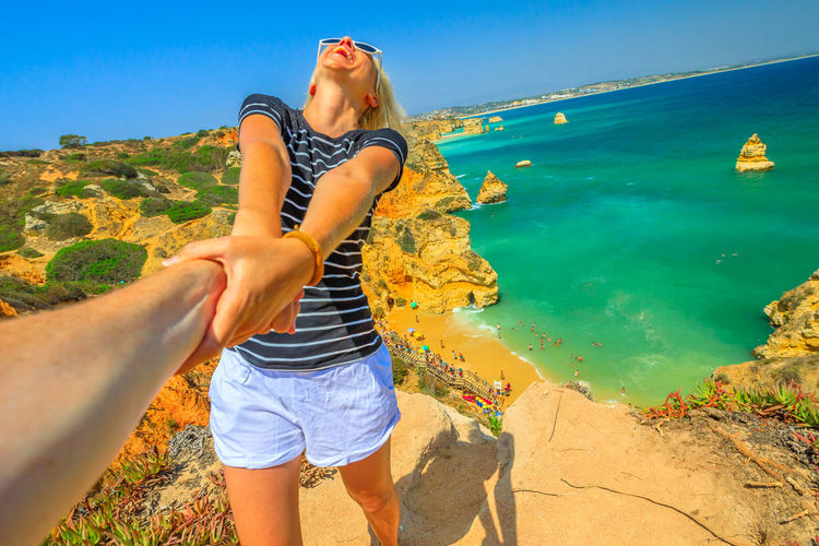 Follow me, woman holding hand at above promontory of Praia Do Camilo in Algarve, Portugal, Europe. Woman freedom at Camilo Beach. Concept of summer holidays and tourist traveler, holding man by hand. Lagos Portugal Algarve Portugal Algarve Coastline Algarve Beach Algarve Cliffs And Beach Beach Sea Town Seascape Boat Portrait Pier Aerial View Cliff Jetty Boats Woman Females Girl Selfie Model Camilo Beach Praia Dona Ana Praia Leisure Activity Water Lifestyles Real People Land One Person Nature Beauty In Nature Casual Clothing Sky Young Adult Women Day Young Women Adult Sunlight Scenics - Nature Outdoors Shorts Human Arm