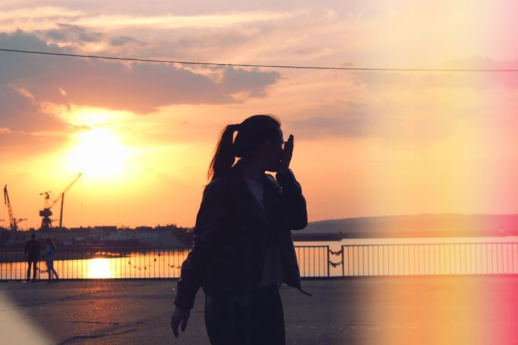 Woman standing on promenade by river against sky during sunset