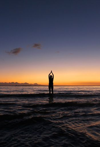 Silhouette Man Doing Yoga At Beach During Sunset