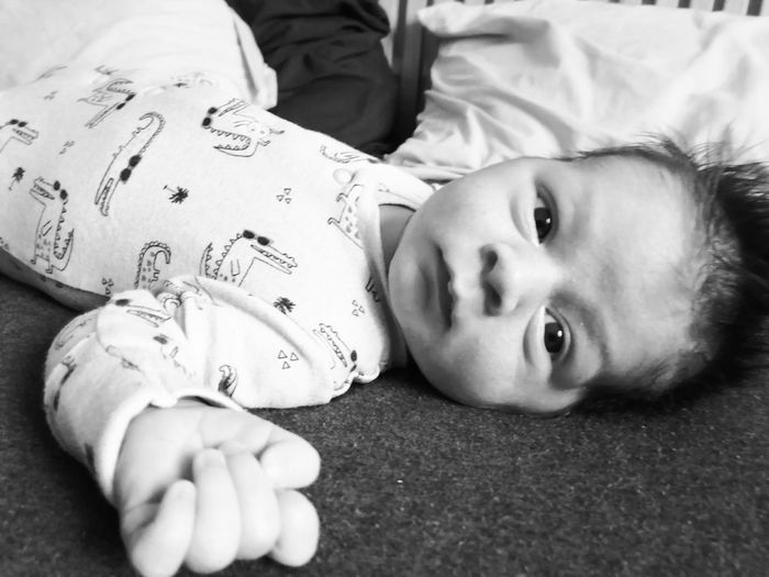 Close-up portrait of cute baby boy lying on bed at home