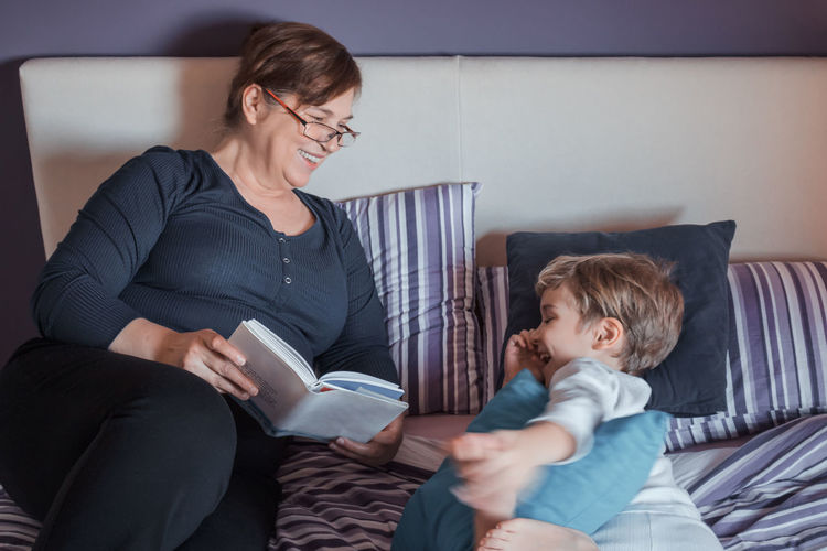 Child Togetherness Indoors  Grandmother Grandson Grandchild Grandparent Love Family Extended Family Multi-generation Family Pyjamas Bedroom Bed Boy Childhood Bonding People Kid Women Mature Adult Positive Emotion Reading Book Storytelling Bedtime Happiness Fun Relaxation Lying Down