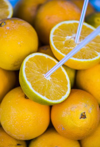 Close-up of drinking straw in oranges