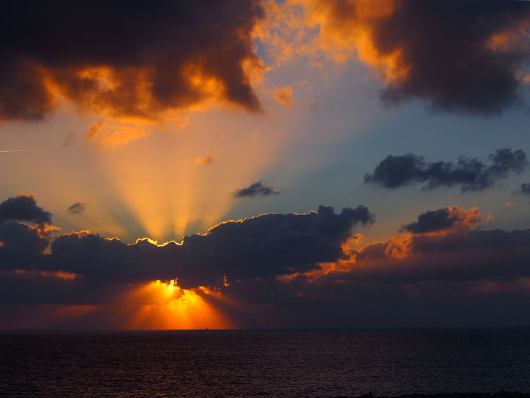 ramatic sunset over the sea with rays of light emerging from dark illuminated clouds over a calm ocean Sky Sunset Cloud - Sky Beauty In Nature Sea Water Tranquility Scenics - Nature Tranquil Scene Horizon Over Water Orange Color Horizon Nature Idyllic No People Waterfront Dramatic Sky Outdoors Non-urban Scene Sun Ominous Dusk