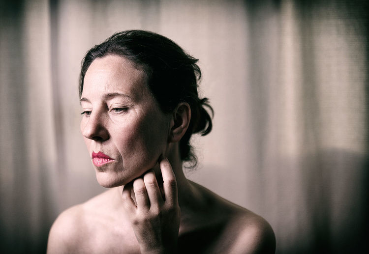 Thoughtful shirtless mature woman against curtain at home