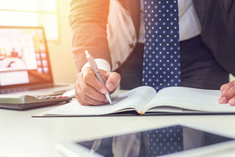 Midsection of business man writing at desk