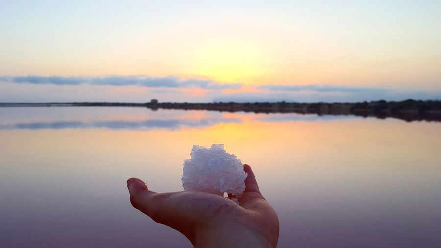 Close-up of hand holding salt against sky during sunset