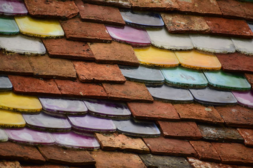 multi colored tiles on a roof Architecture Backgrounds Brick Brick Wall Building Exterior Built Structure Close-up Creativity Day Full Frame Graffiti Low Angle View Multi Colored No People Outdoors Pattern Roof Tile Textured  Wall Wall - Building Feature