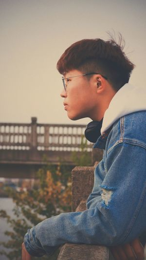 Side view of young man looking away against sky