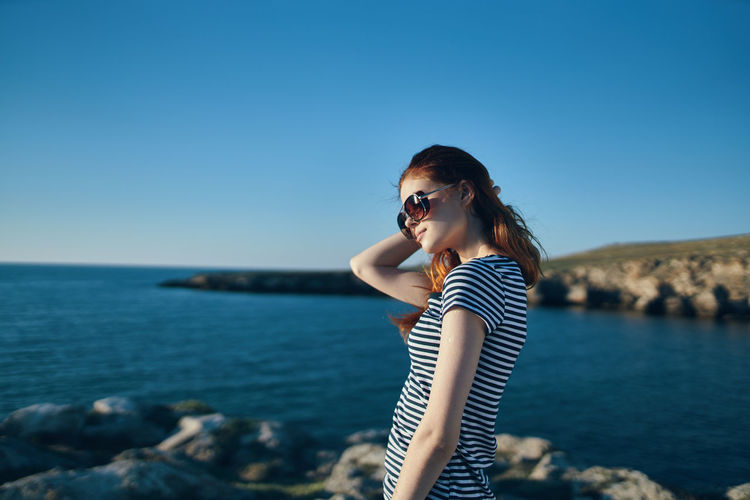 Young woman wearing sunglasses standing by sea against clear blue sky
