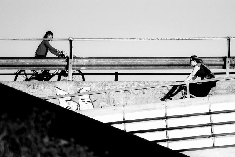 People sitting on railing by sea against clear sky