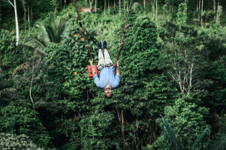 Man hanging on tree in forest