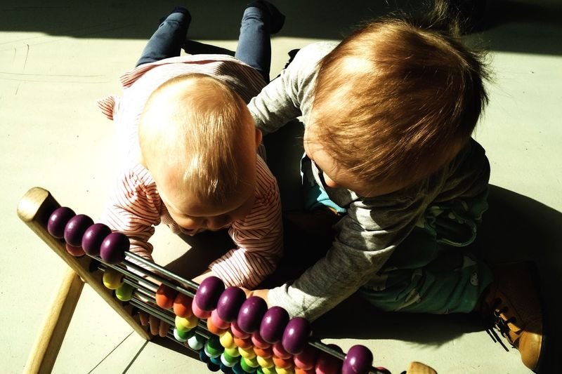 Siblings playing with abacus in home