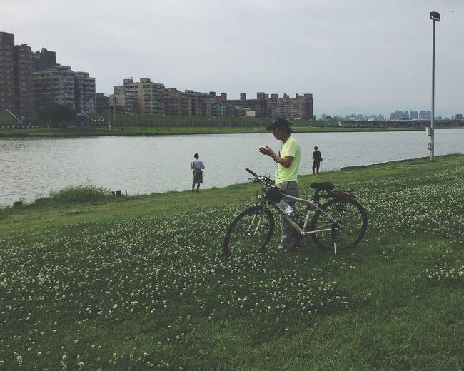 Biker at the riverside. Biker Riverside Water Bicycle Architecture Nature Building Exterior Sky Grass Men