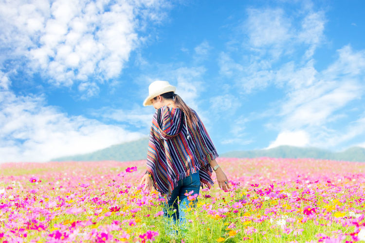 Woman standing by pink flowering plants on field against sky