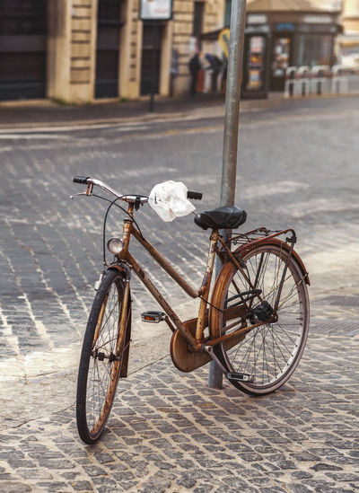 Bicicletta Transportation Mode Of Transportation City Street Bicycle Land Vehicle Architecture Focus On Foreground Building Exterior Day Built Structure Footpath Stationary Outdoors Cobblestone Building Sidewalk Parking Wheel Paving Stone