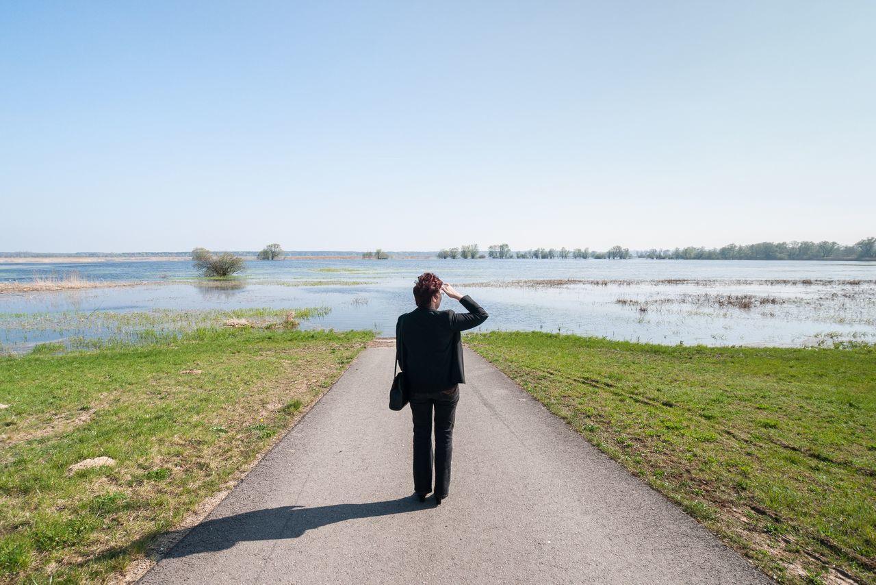 Rear view full length of woman standing against flooded road