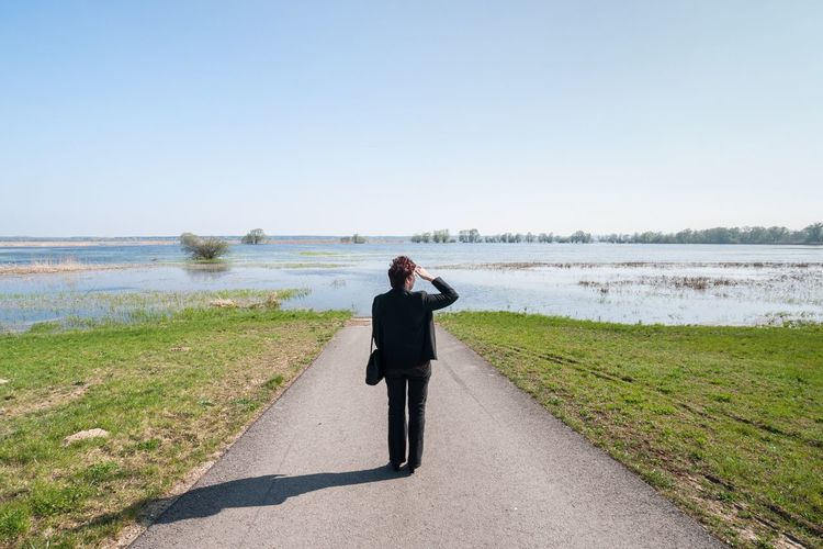 Leading Lines Flooded Road Flooded Road Blue Sky Woman Gaze into the Distance How Do You See Climate Change? Brandenburg Germany Water Sunny Day Clear Blue Sky Horizon Over Water Landscape Landscape_photography Learn & Shoot: Leading Lines Landscapes With WhiteWall