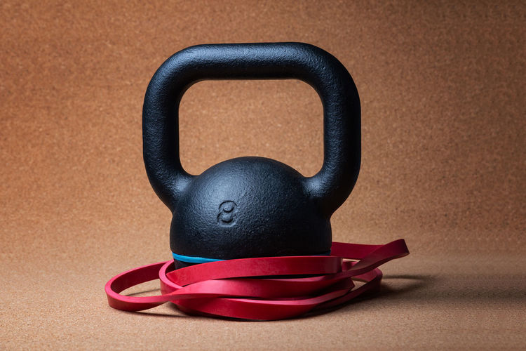 Close up view of a kettlebell and a Resistance band - studio shot Band Resistance  Bands Blue Brown Close-up Colored Background Connection Crossfit Equipment Fit Fitness Indoors  Kettlebell  Muscles No People Red Single Object Still Life Strength Studio Shot Table Training Two Objects Wood - Material
