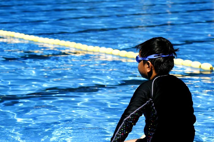 young kid with goggles swimming in a swimming pool Active Athlete Boy Child Exercise Floaters Floating On Water Goggles Health Kid Recreation  Splash Splashing Sports Swim Swimmer Swimming Pool Water Water Sports Wet Young Youth