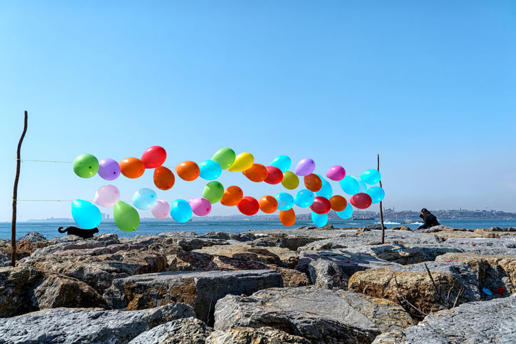 Multi colored balloons on rock by sea against clear blue sky