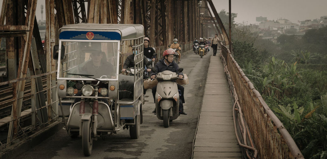 Tucktuck driver in the early morning crossing Red River Bridge in Ha Noi. Architecture ASIA Bridge Built Structure City Day Holiday Land Vehicle Large Group Of People Men Mode Of Transport Motorcycle Nature Outdoors People Real People Scooter Sky The Way Forward Transportation Travel Tree Tucktuck Vietnam Women