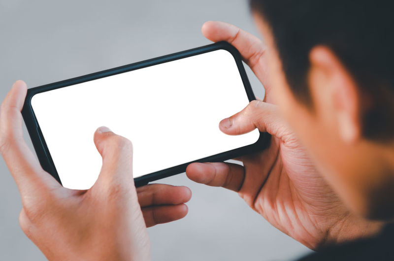 Midsection of man using mobile phone