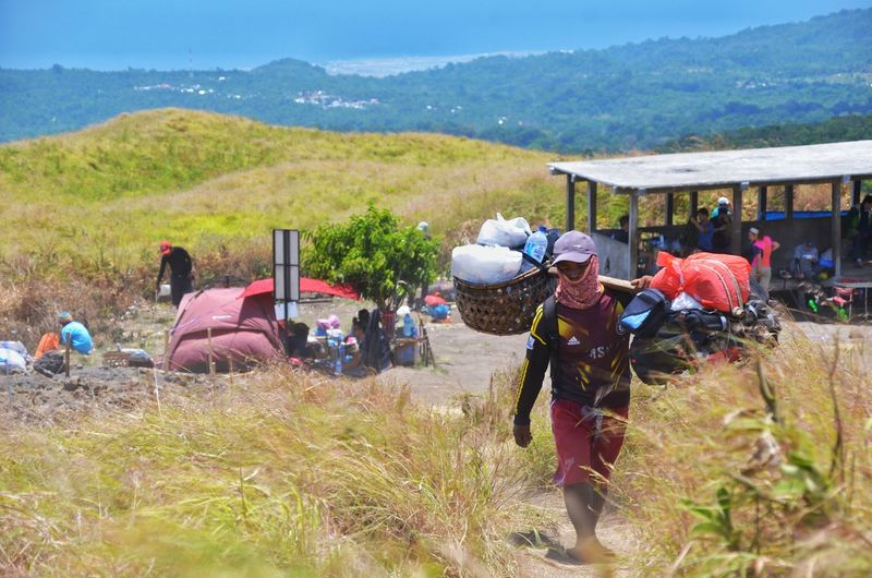 MOUNT RINJANI, LOMBOK INDONESIA. SEPT 16th 2017- A porter hikes up the mountain, carrying the tourist stuff via Sembalun route. Mount Rinjani Sembalun Hiking Hikingadventures Wallpaper Background Mountain Men Farmer Rural Scene Women Working Occupation Agriculture Sky Landscape Tent Camping Camping Stove Explorer Hiker Hiking Pole Backpack