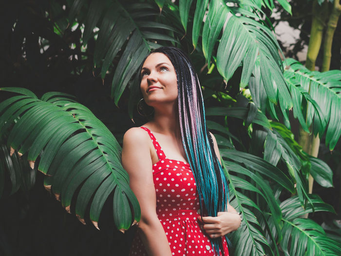 Thoughtful woman with dreadlocks standing against plants