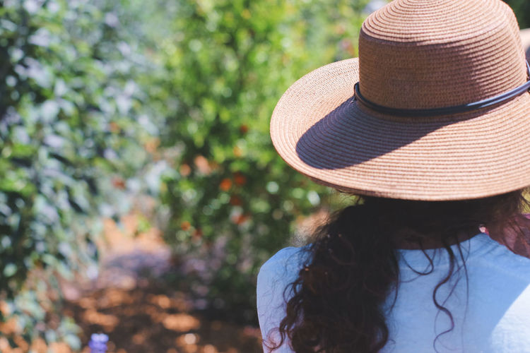 Walking in the garden California Candid Photography Close-up Day Focus On Foreground Hat Headshot Leisure Activity Lifestyles Nature One Person Outdoors People Real People Rear View Sun Hat Tree USA Women Young Adult Young Women Breathing Space Investing In Quality Of Life