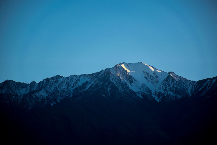 The snowcapped mountains of Leh ladakh look absolutely majestic during the sunrise. The way the light hits the mountain peak in the blue sky is a landscape not to be missed. Ladakh is full of mountains and lakes and is the best travel destination for someone who desires peace and adventure. Mountain Sky Beauty In Nature Scenics - Nature Mountain Range Blue Tranquility Tranquil Scene Non-urban Scene Clear Sky Nature Cold Temperature Mountain Peak Landscape Snowcapped Mountain Snow Outdoors Leh Ladakh Himalayas Sunrise Winter India Sunlight Hills A New Perspective On Life Holiday Moments EyeEmNewHere