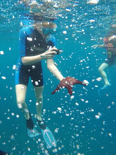 Man Photographing Starfish In Sea At Galapagos Islands