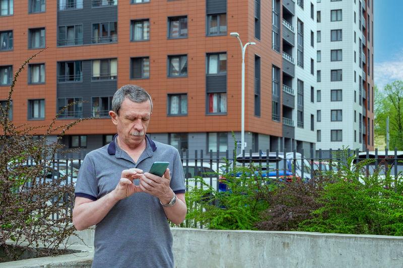 Full length of man using mobile phone in city