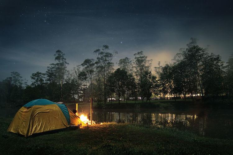 Camping tent by lake at dusk