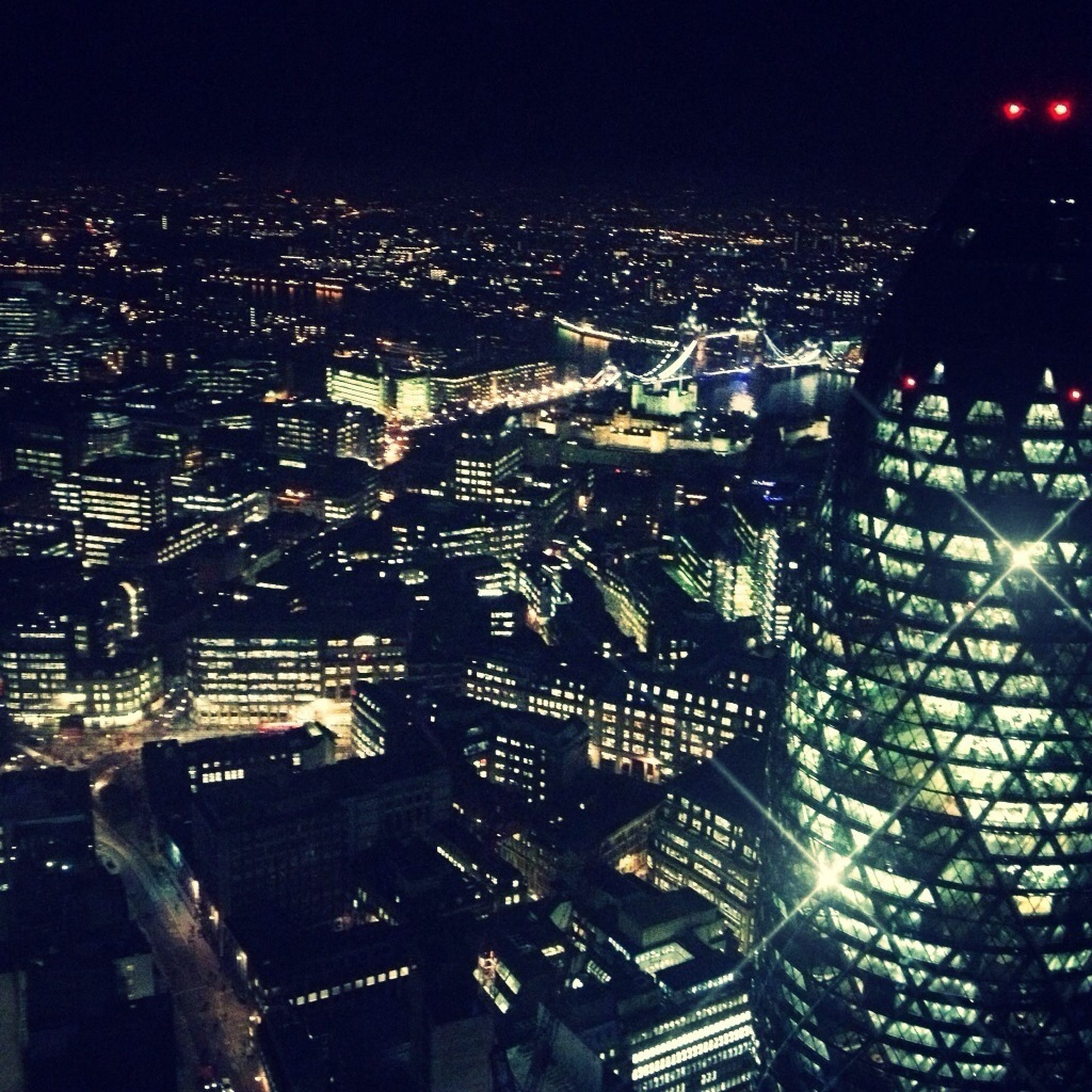 night, illuminated, city, cityscape, building exterior, architecture, built structure, crowded, high angle view, city life, skyscraper, residential district, capital cities, modern, aerial view, office building, residential building, sky, outdoors, travel destinations