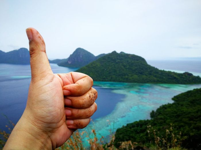 Close-up of cropped hand showing thumbs up by sea against sky