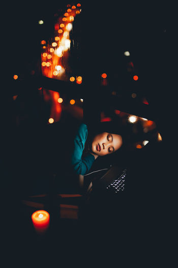 High Angle View Of Young Woman Sleeping By Window In Darkroom At Home