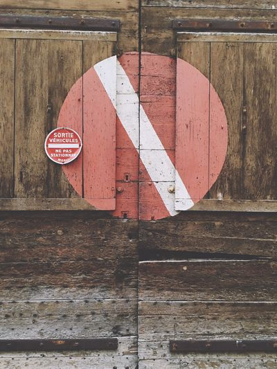 No entry sign on closed wooden door