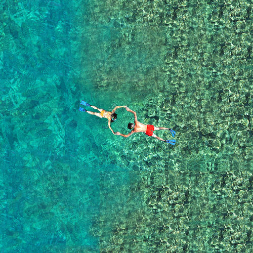 High angle view of couple holding hands and floating on sea