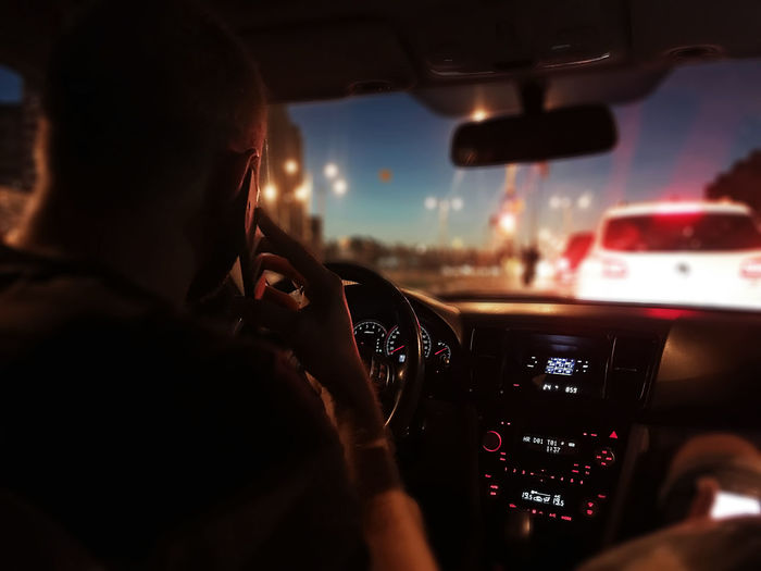 Rear view of man driving while talking on mobile phone in car at night